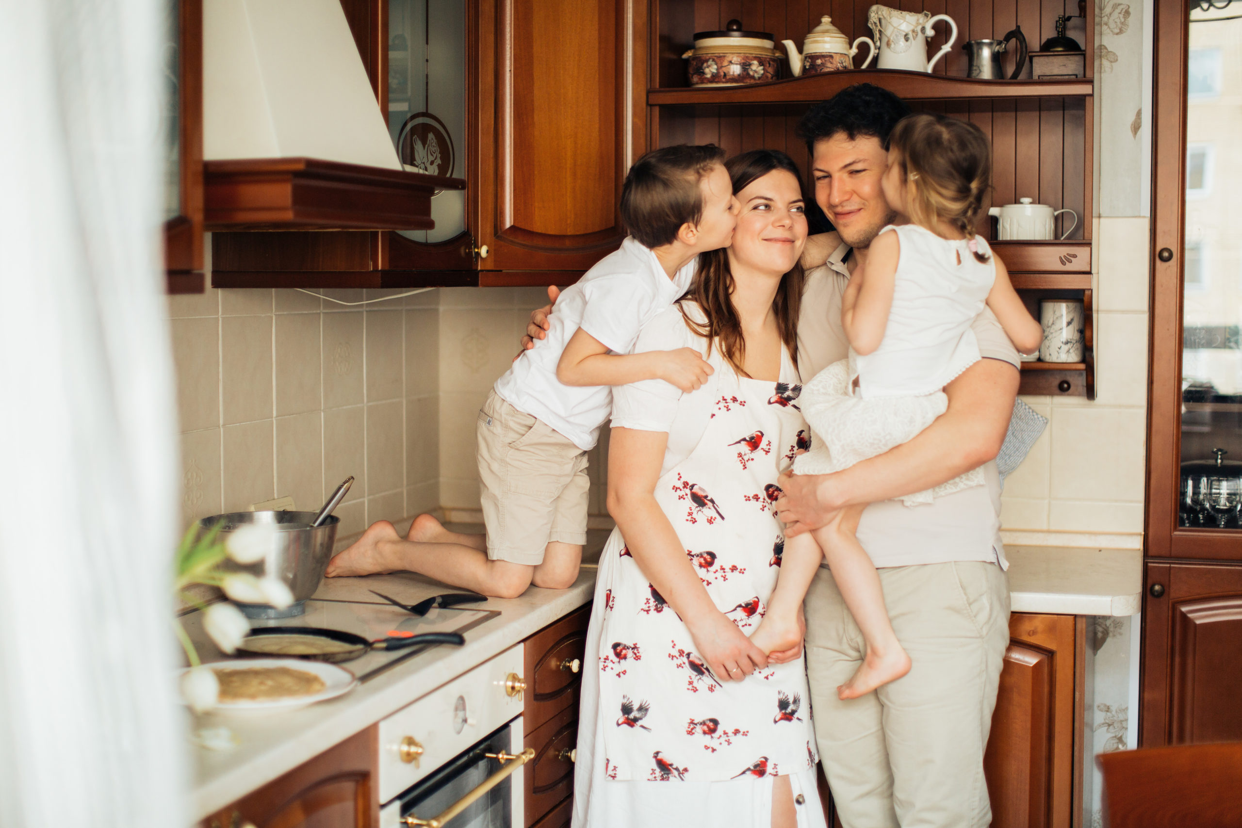 Helping Your Kids During Coronavirus Social Distancing Photo of kids kissing their parents